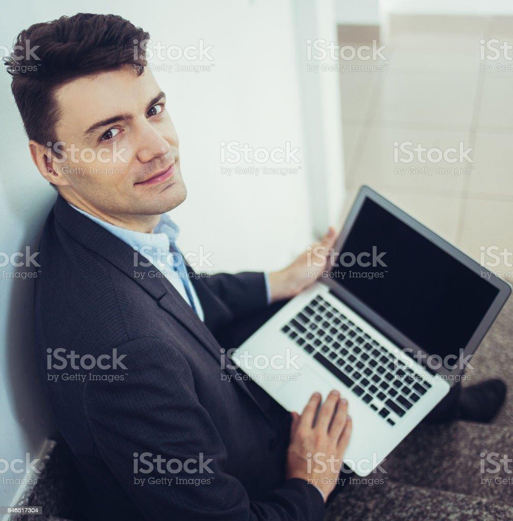 b0dd4489eb Homme d'affaires souriant tenant ordinateur portable sur les genoux et  regardant la caméra dans