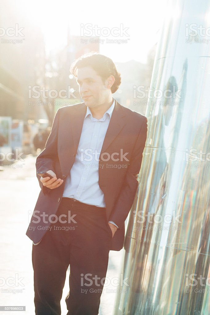 Smiling businessman holds a smartphone, leans at Contemporary column stock photo