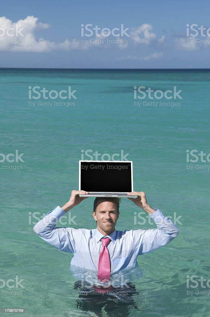 Smiling Businessman Holds Laptop on Head in Sea royalty-free stock photo