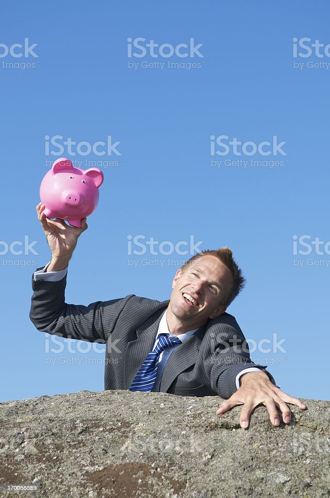 Smiling Businessman Holds Piggy Bank on Mountaintop royalty-free stock photo