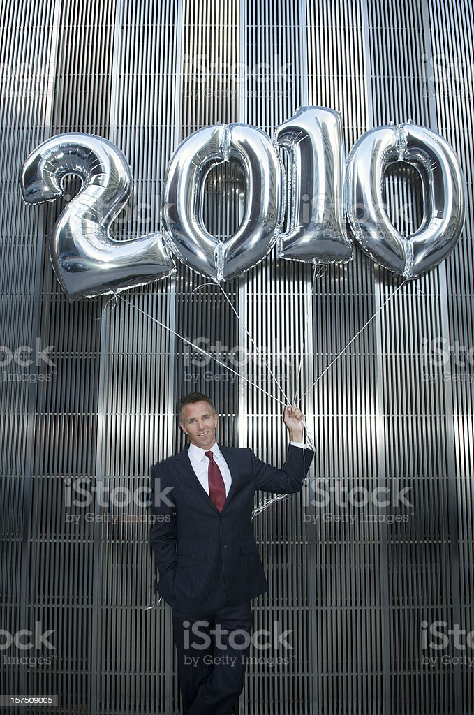 Smiling Businessman Holds Shiny 2010 Balloon Bouquet stock photo