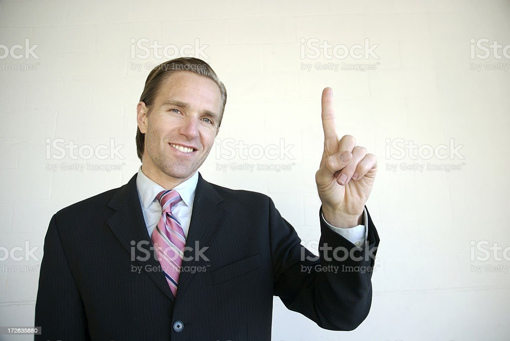 Smiling Businessman Holds Up Number One Success Finger royalty-free stock photo