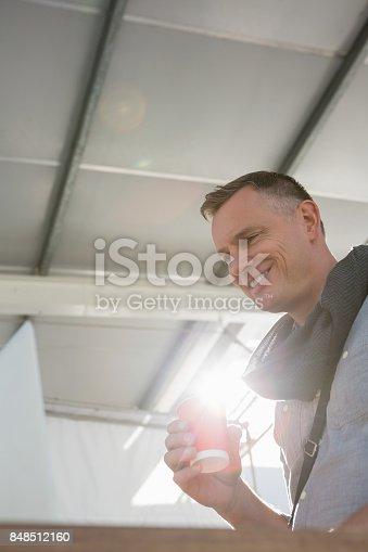 istock Smiling businessman hving drink at desk in office 848512160