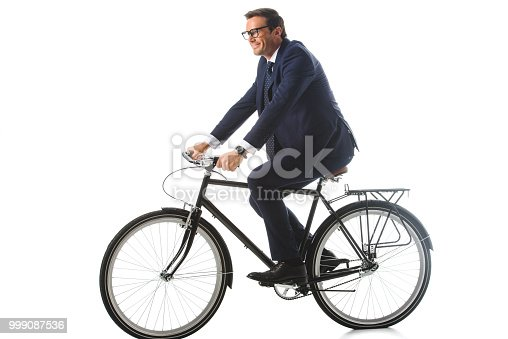 istock smiling businessman in eyeglasses riding bicycle isolated on white background 999087536