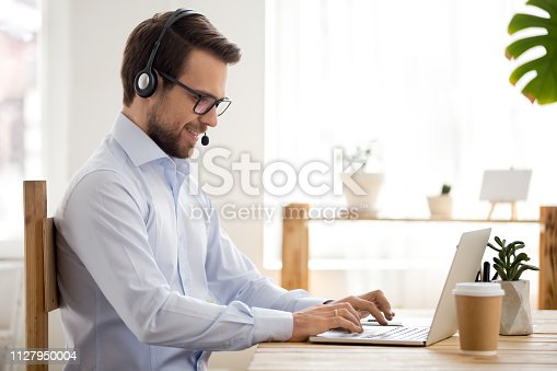 Smiling businessman in headset working on laptop make conference video call using computer, friendly professional operator salesman consulting client online, customer service support helpline concept