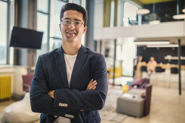 Smiling businessman in his office with his arms crossed stock photo