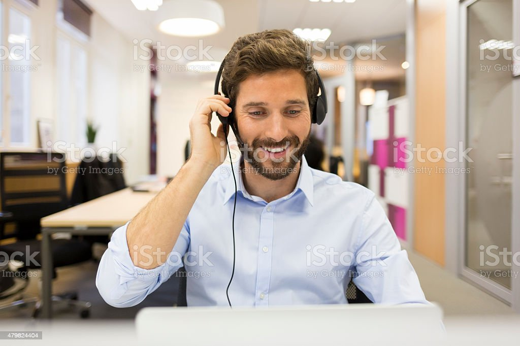 Smiling Businessman in the office on video conference, headset, stock photo