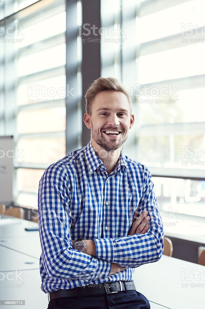 Smiling businessman in the office Portrait of friendly businessman wearing checkered shirt sitting with arms crossed in a board room in an office and smiling at camera.  2015 Stock Photo