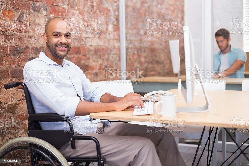 Lächelnd Geschäftsmann am Rollstuhl Arbeiten an seinem Schreibtisch – Foto