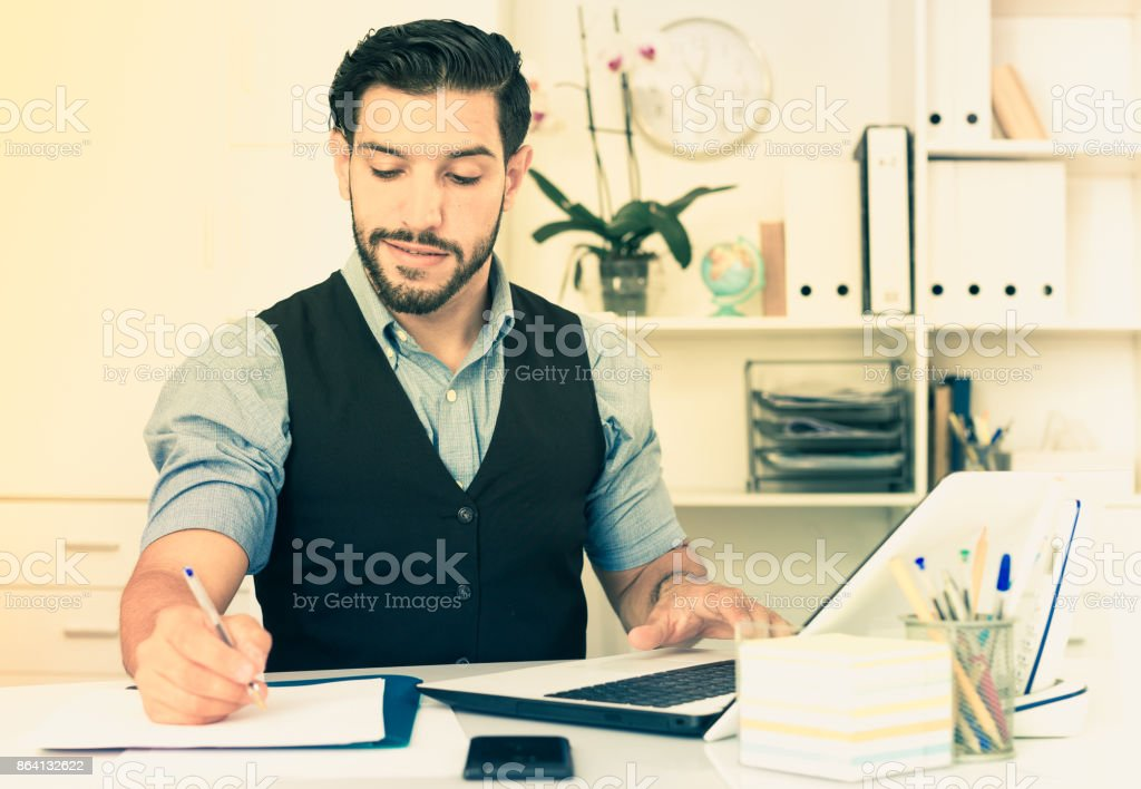 Smiling businessman is working behind laptop and reading documents royalty-free stock photo