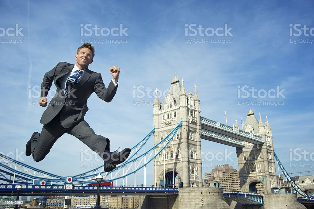 Smiling Businessman Jumps Over Tower Bridge London royalty-free stock photo