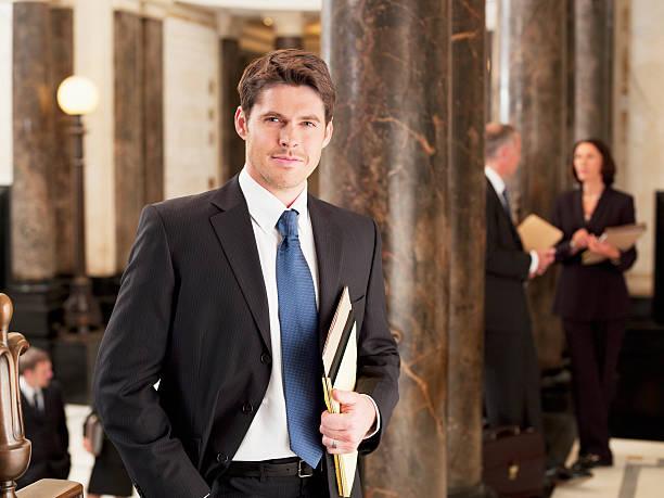 smiling businessman leaning against pillar in corridor - four lawyers stockfoto's en -beelden