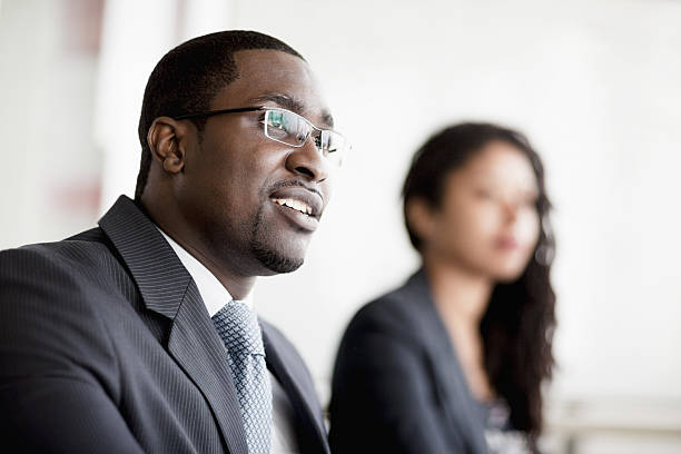 Smiling businessman listening at a business meeting stock photo