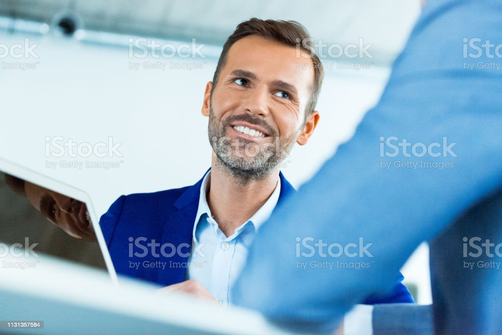 Smiling businessman looking at colleague in office Smiling mature businessman looking at colleague during meeting. Male professionals are discussing strategy. They are working at creative office. 30-39 Years Stock Photo