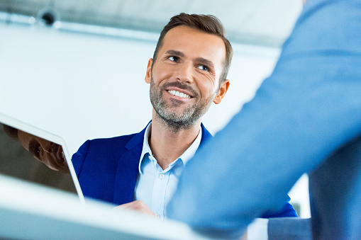 Smiling Businessman Looking At Colleague In Office Stock Photo - Download Image Now