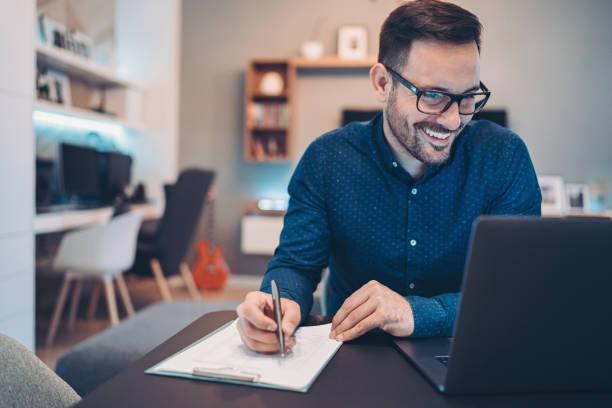 Lächelnder Geschäftsmann schaut auf seinen Laptop und schreibt in ein Dokument – Foto