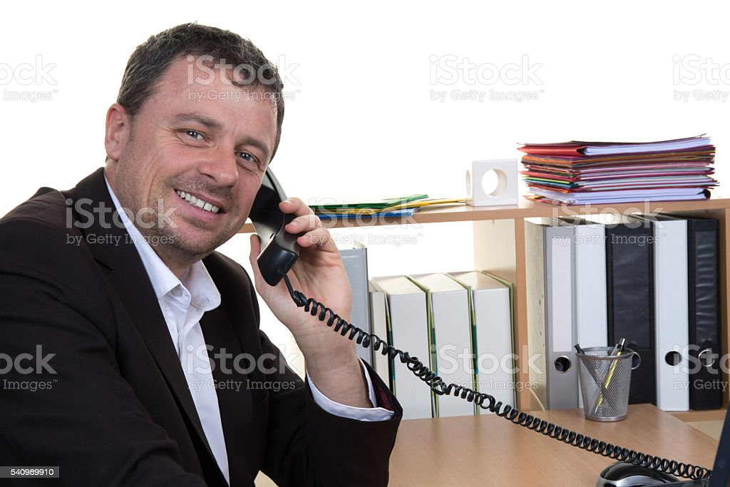Smiling businessman looking at the camera while on the phone stock photo