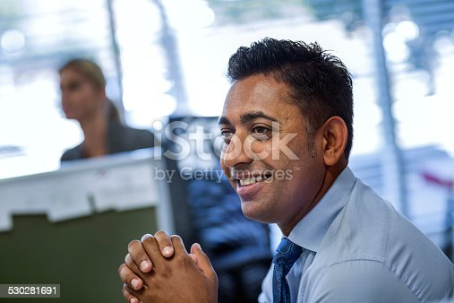 Smiling businessman with hands clasped looking away in office