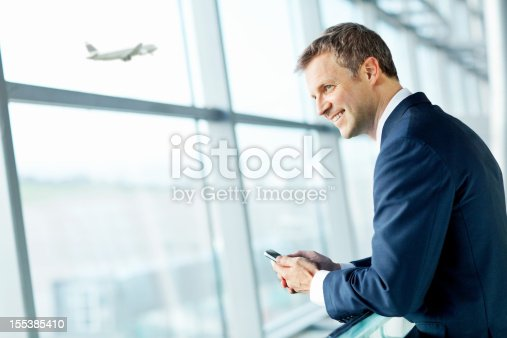 istock Smiling Businessman Looking Out Airport Window. 155385410