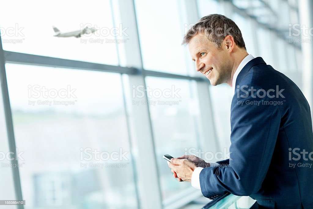 Smiling Businessman Looking Out Airport Window. stock photo