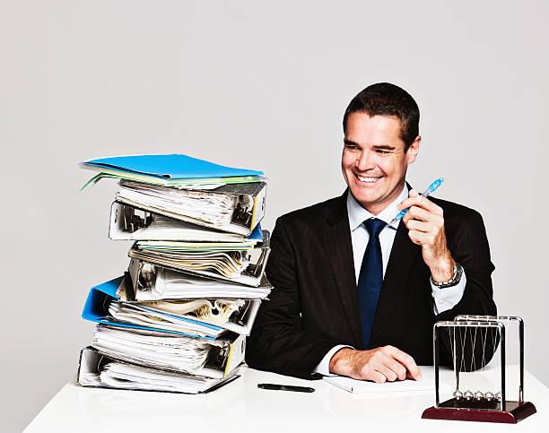 lächelnd geschäftsmann sieht selbstbewusst in großen stapel von dateien - bic kugelschreiber stock-fotos und bilder