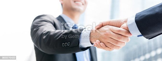 istock Smiling businessman making handshake with his partner outdoors in the city 955576400