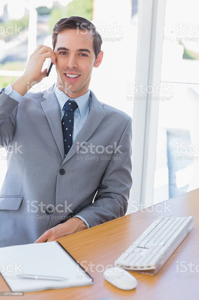 Smiling businessman on the phone looking at camera royalty-free stock photo