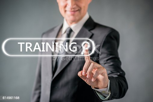 istock Smiling businessman pointing at virtual  Training word 614961168