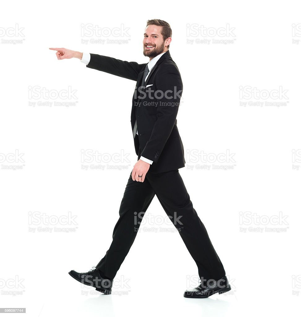 Smiling businessman pointing away royalty-free stock photo