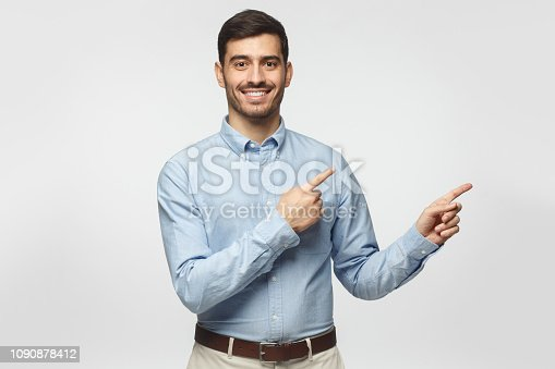 Smiling businessman pointing right with two hands and looking at camera, isolated on gray background