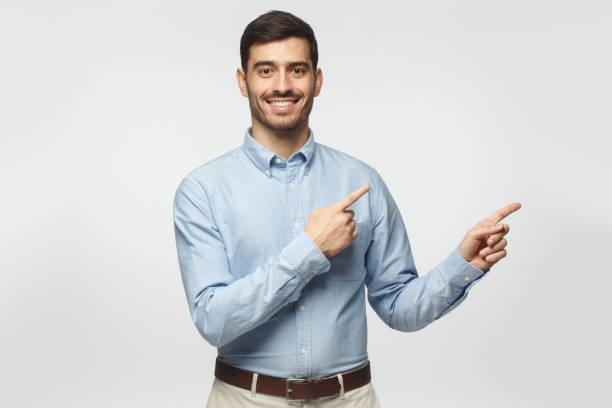 灰色の背景に分離された実業家の両手で右を指しているとカメラを見て笑みを浮かべて、 - 指差す ストックフォトと画像
