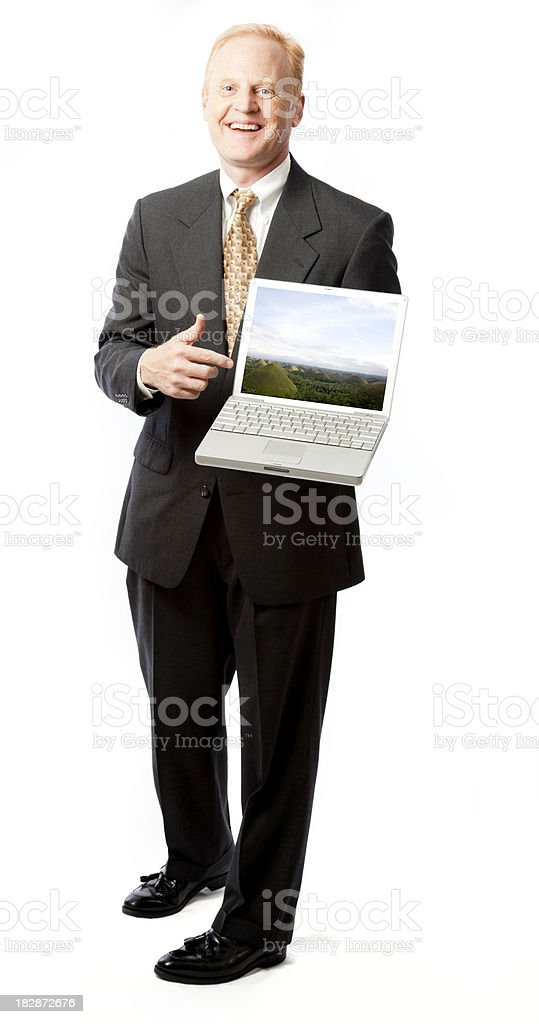 Smiling Businessman Points at Laptop (with clipping path) royalty-free stock photo