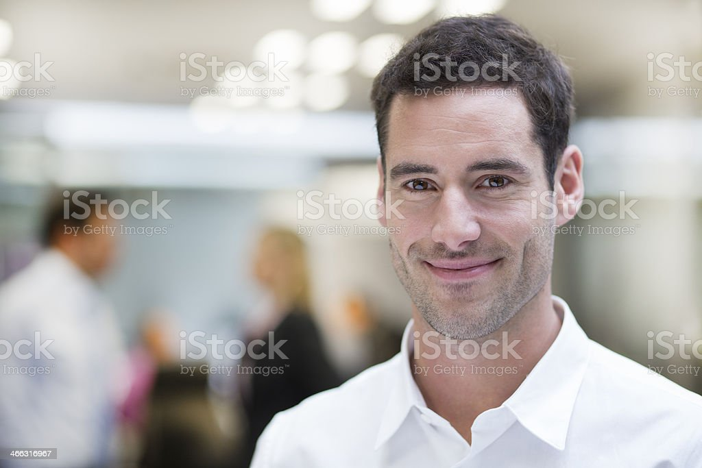 Smiling Businessman posing while colleagues talking together in background stock photo