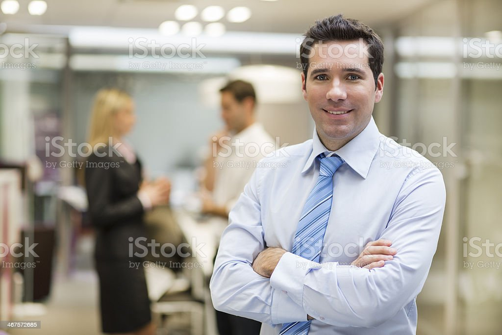 Smiling Businessman posing while colleagues talking together in stock photo