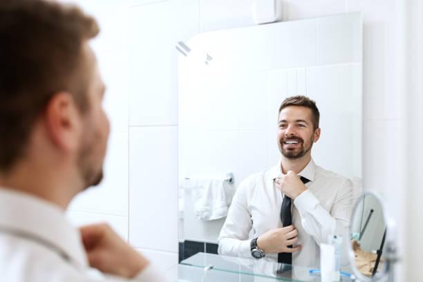 souriant, homme d'affaires mise sur la cravate tout en regardant dans le miroir et, debout dans la salle de bain. - miroir photos et images de collection