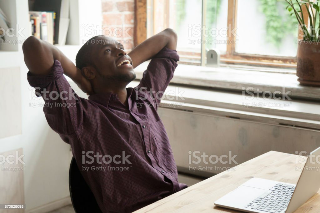 Smiling businessman relaxing at workplace in modern office. stock photo