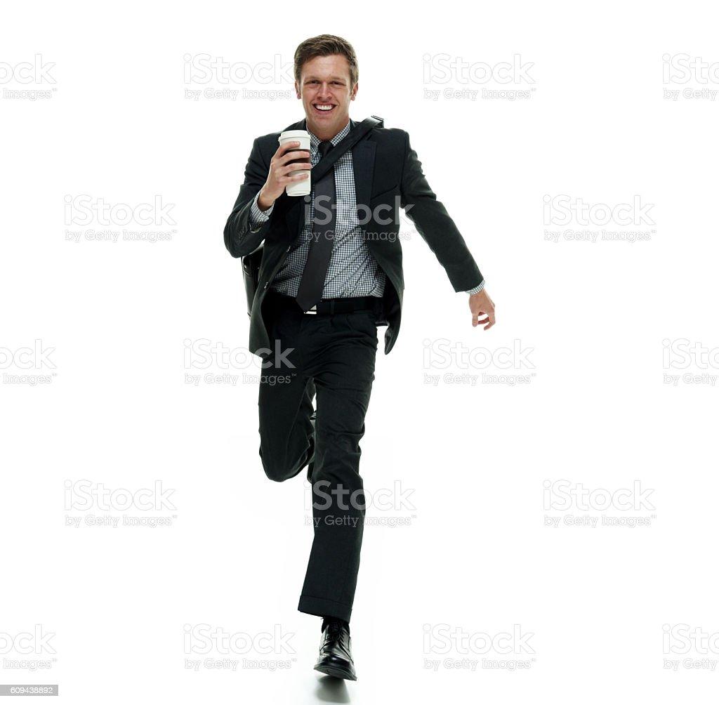 Smiling businessman running stock photo
