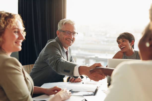 Smiling businessman shaking hands with a colleague during a meeting stock photo