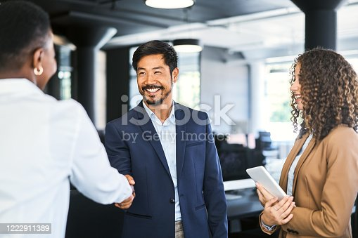 Smiling businessman shaking hands with female professional. Young businesswoman is holding digital tablet. They are standing at office.
