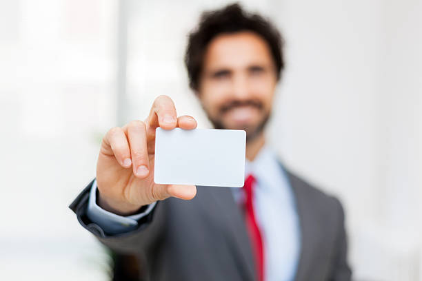 Smiling businessman showing a blank card - foto de acervo