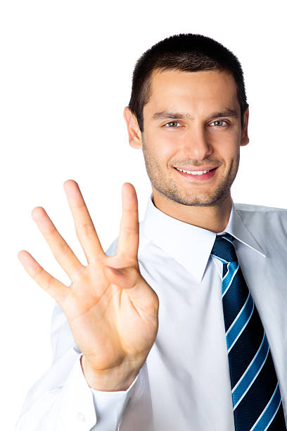 Smiling businessman showing four fingers stock photo