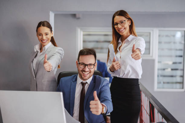 Smiling businessman sitting and showing thumbs up. Two female colleagues standing next to him and holding thumbs up. Office interior. If you do what you always did, you will get what you always got. Smiling businessman sitting and showing thumbs up. Two female colleagues standing next to him and holding thumbs up. Office interior. If you do what you always did, you will get what you always got. diad stock pictures, royalty-free photos & images