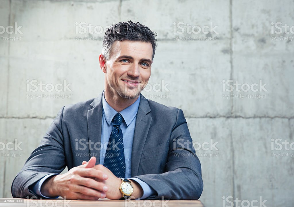 Smiling businessman sitting at the table stock photo