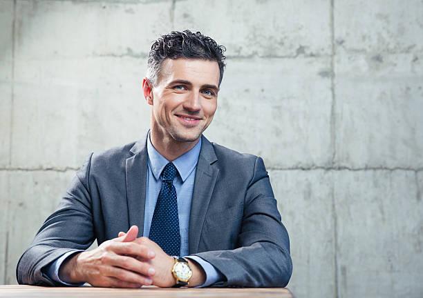 Sorridente Empresário sentando na mesa - foto de acervo