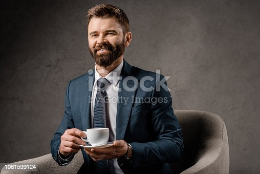 1081599130 istock photo smiling businessman sitting in armchair with cup of coffee 1081599124