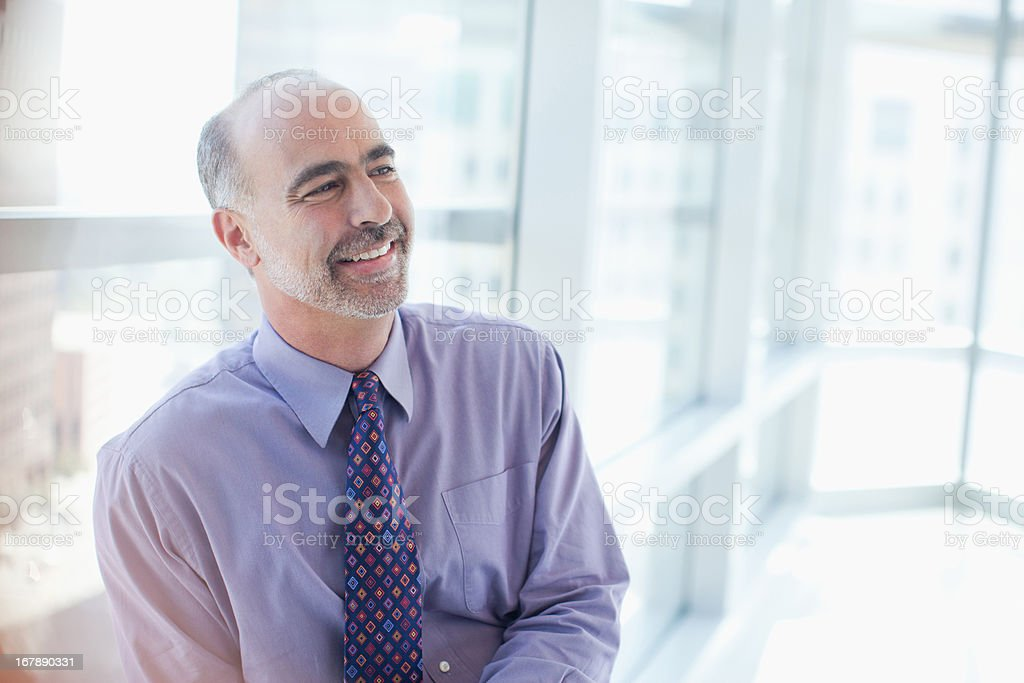 Smiling businessman sitting in office stock photo