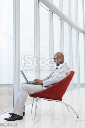 1053499704 istock photo Smiling businessman sitting on chair and using laptop 176113495
