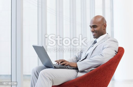 1053499704 istock photo Smiling businessman sitting on chair and using laptop 182190236