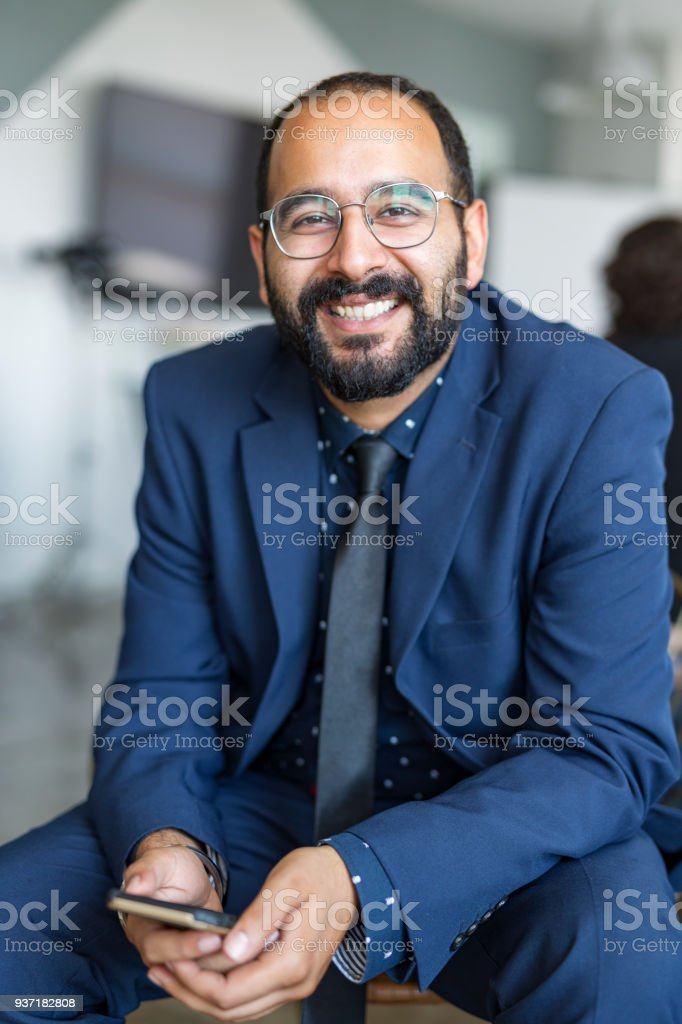 Smiling Businessman Sitting With his Mobile Telephone stock photo