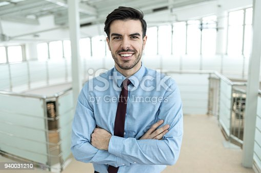 825082848istockphoto Smiling businessman standing arms crossed in office 940031210